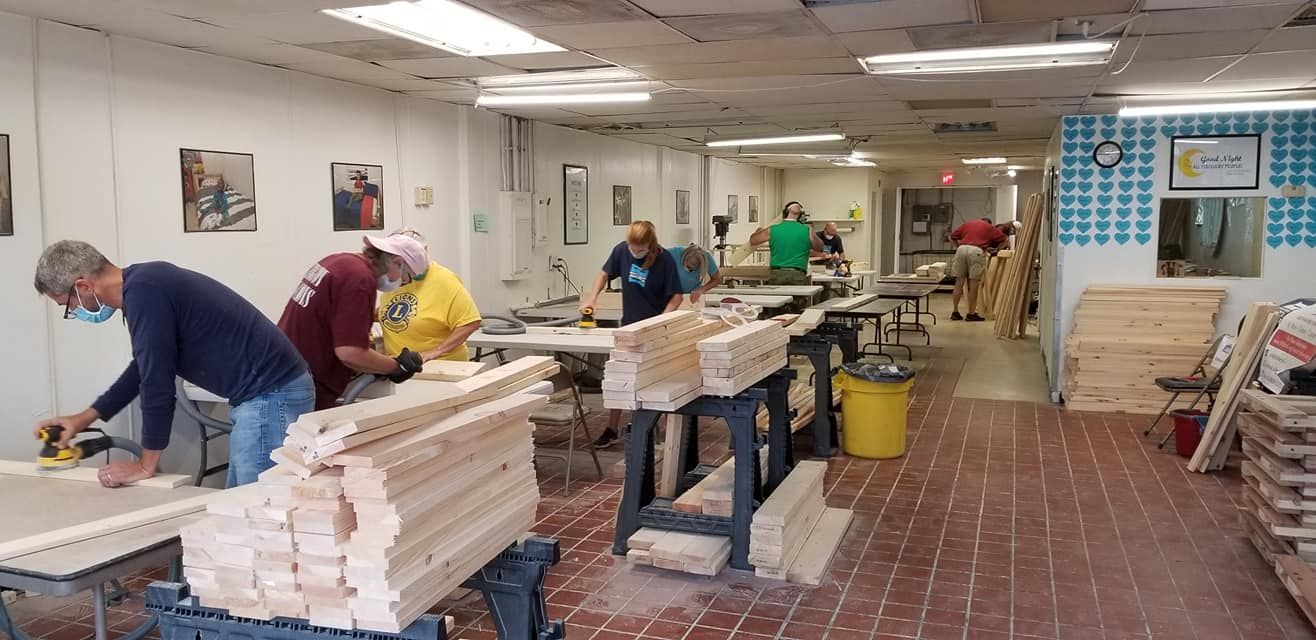Lions Club members building beds for charity